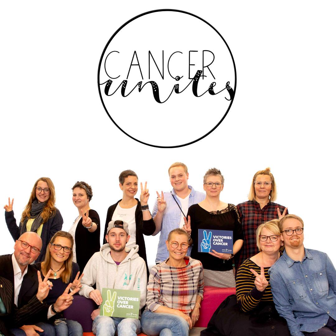 Gruppenfoto von 12 Krebsbloggern mit Logo im Hintergrund