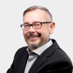 Porträtfoto eines Mannes mit grau melierten kurzen Haaren, Bart und Brille