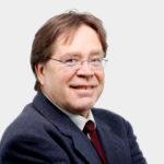 Porträtfoto eines Mannes mit braunen kurzen Haaren und Brille