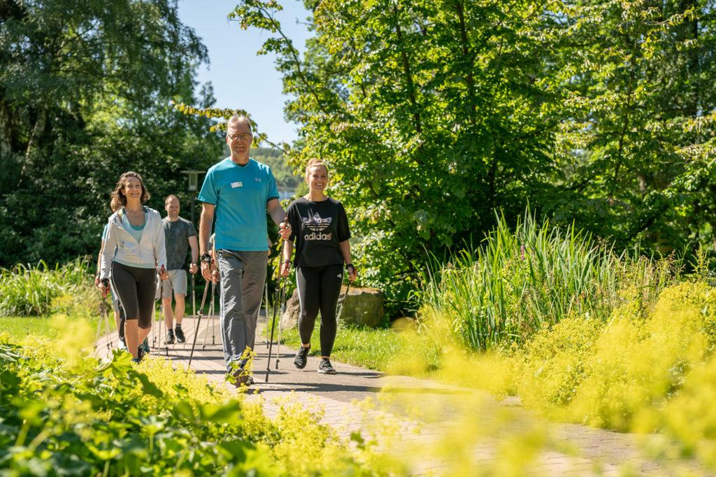 Frauen und Männer beim Nordic Walking im Park