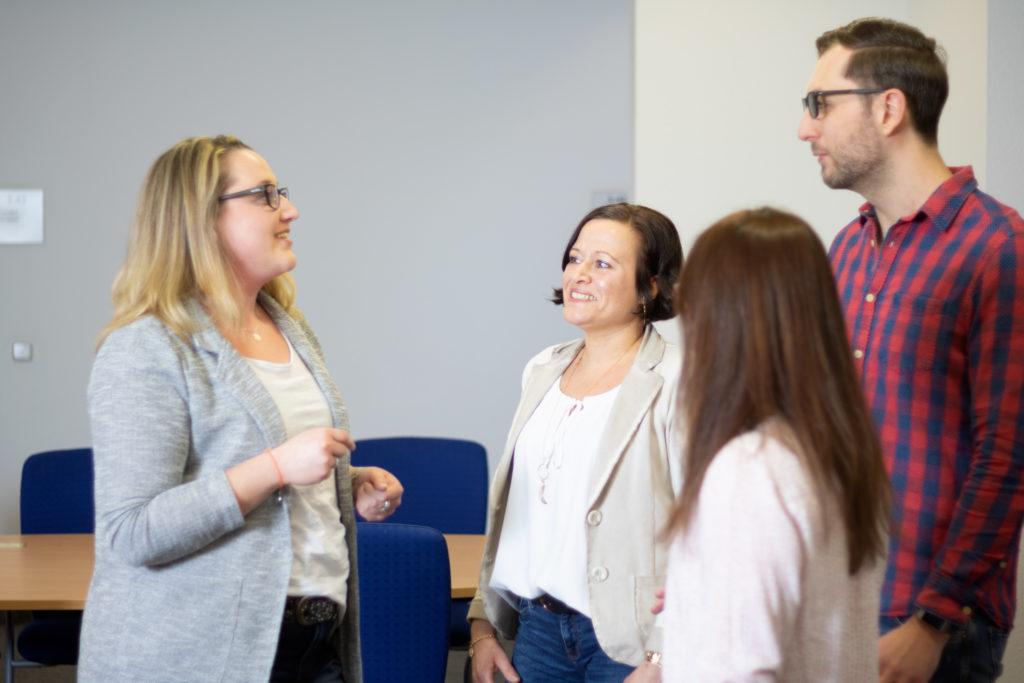 Drei Frauen und ein Mann stehen zusammen im Gespräch