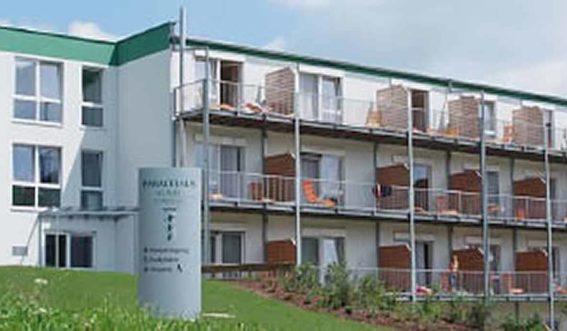 Klinikgebäude mit Balkonen am Hang im Allgäu
