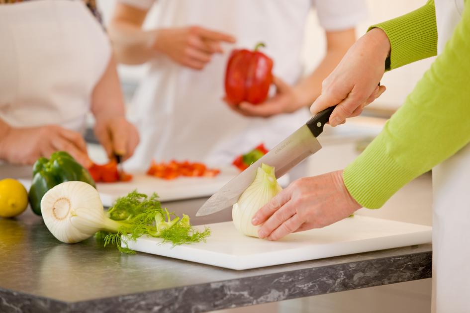 Hände von drei Personen, die an einer Arbeitsplatte auf Brettchen Fenchel und Paprika schneiden