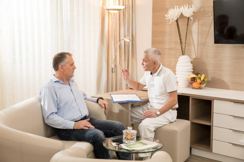 Rehabilitand mit einem Arzt sitzend im Gespräch