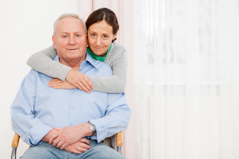 Dunkelhaarige Frau umarmt älteren Mann auf einem Stuhl