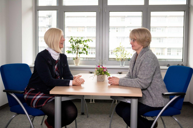 Zwei blonde Frauen sitzen sich am Tisch gegenüber