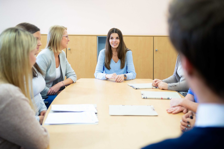 Frau mit dunklen langen Haaren leitet eine Besprechung am Konferenztisch