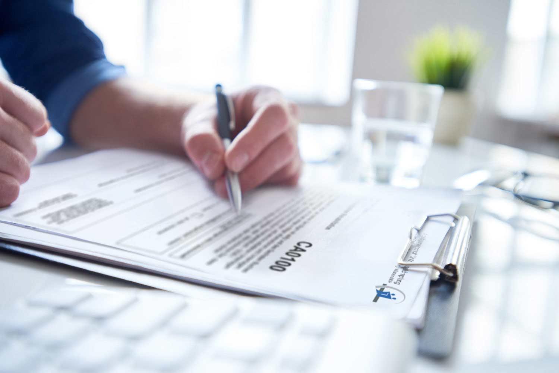 Männliche Hand mit Kugelschreiber beschriftet Formular auf Klemmbrett