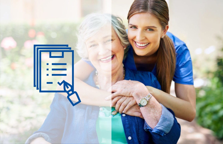 Dunkelhaarige Frau im blauen Kittel umarmt ältere Frau im Rollstuhl