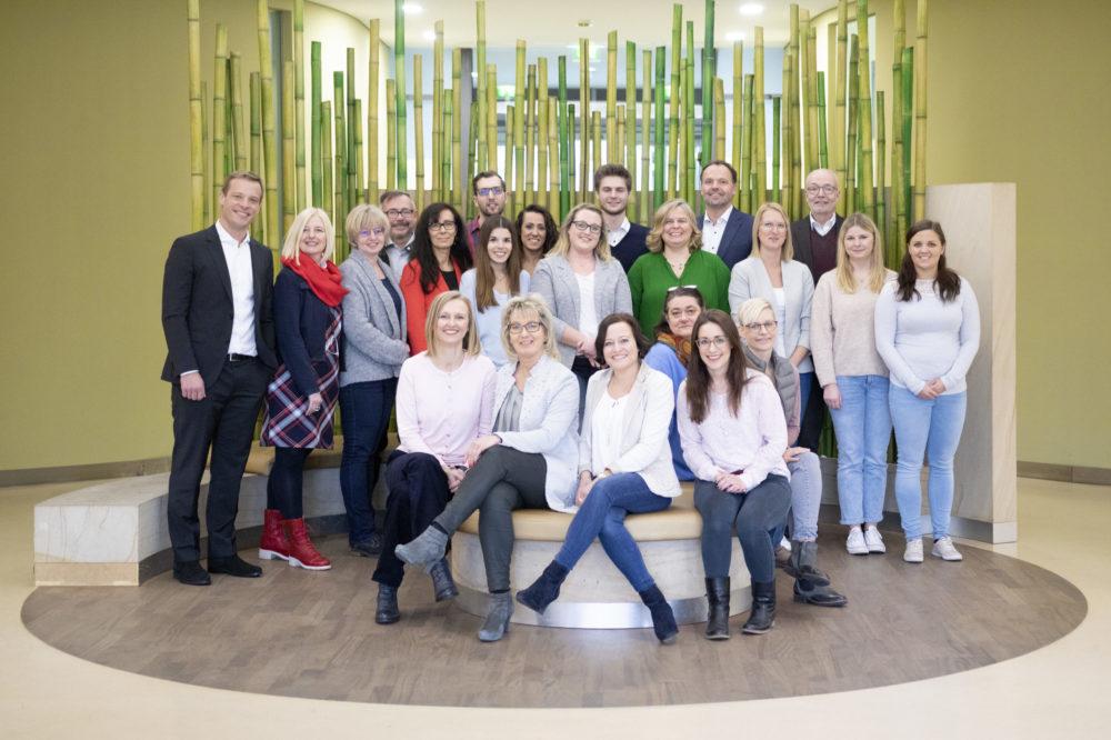 Gruppenbild zeigt Mitarbeiterinnen und Mitarbeiter im Foyer der Geschäftsstelle