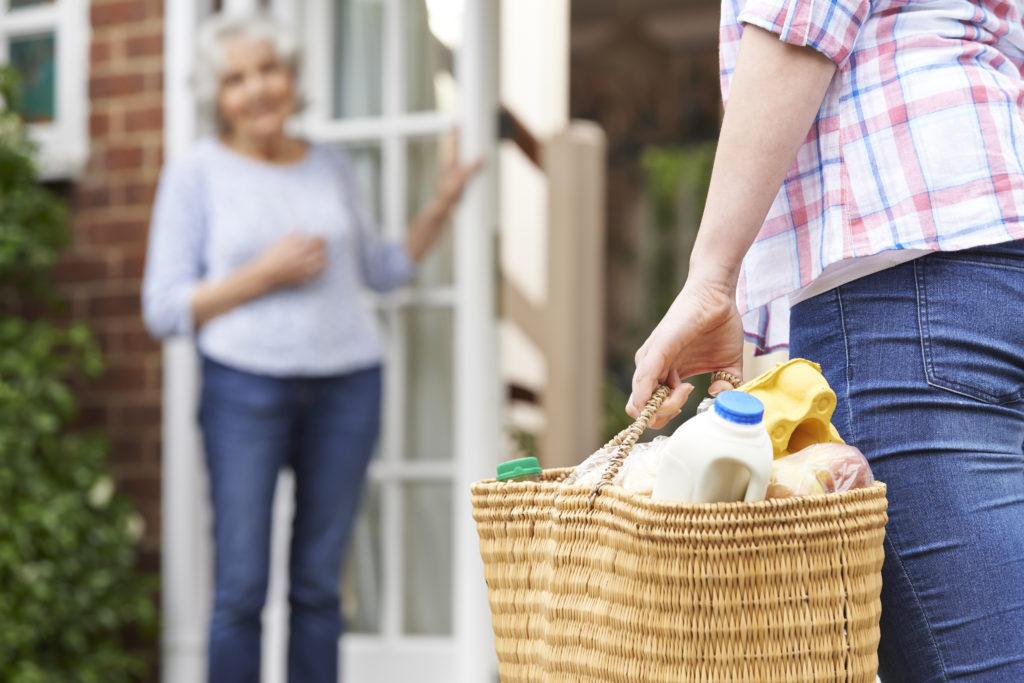 Frau bringt älterer Dame Einkäufe in einem Korb nach Hause