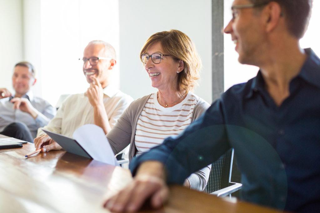Eine Frau und drei Männer besprechen sich lächelnd am Konferenztisch