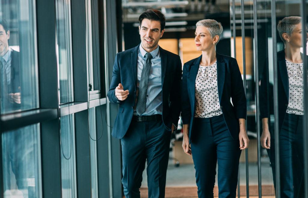 Frau und Mann mittleren Alters gehen im Gespräch einen Büroflur entlang