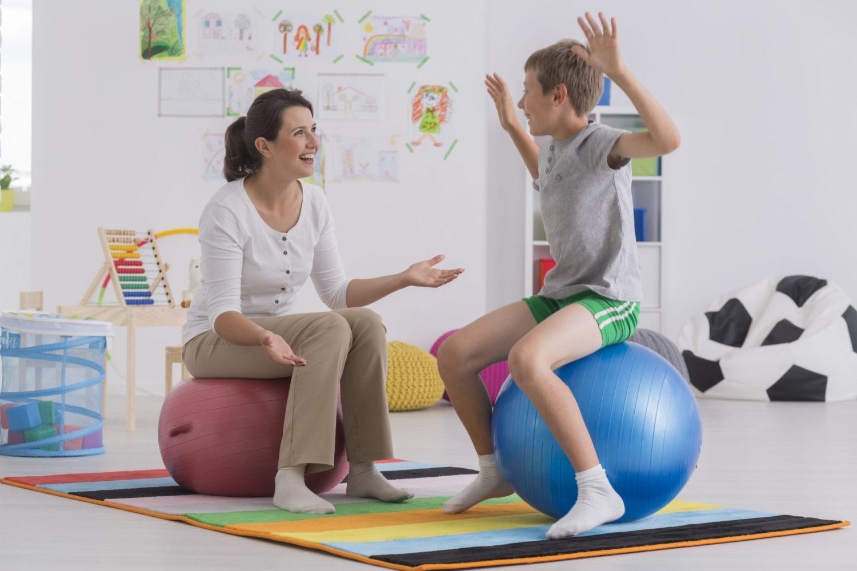 Blonder Junge und dunkelhaarige Frau sitzen auf Gymnastikbällen im Übungsraum