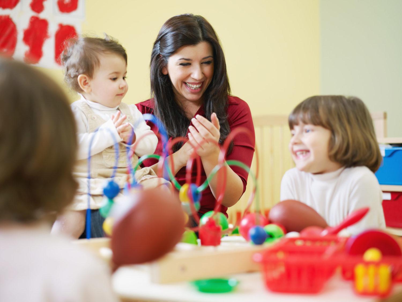 Dunkelhaarige Frau spielt mit drei kleinen Kindern