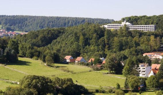 Klinikgebäude am Hang umgeben von Wald