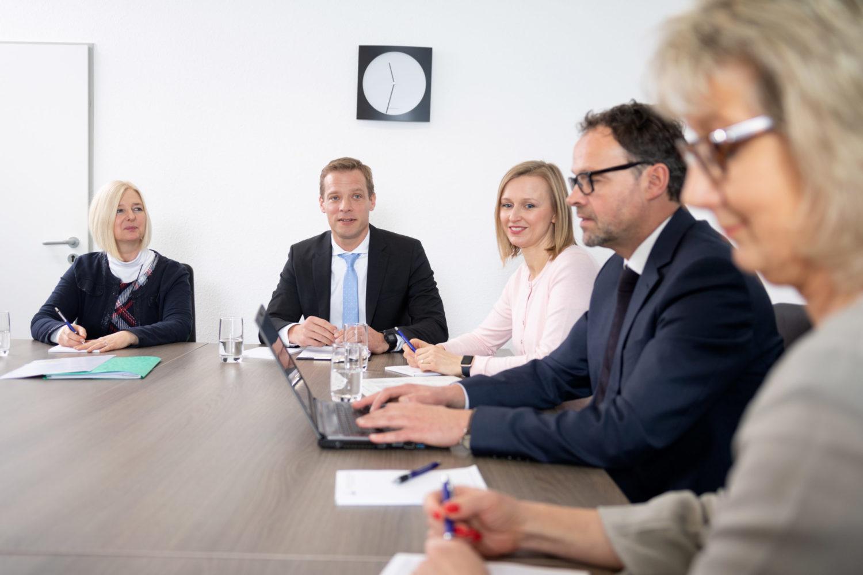 Drei Frauen und zwei Männer sitzen an einem Besprechungstisch