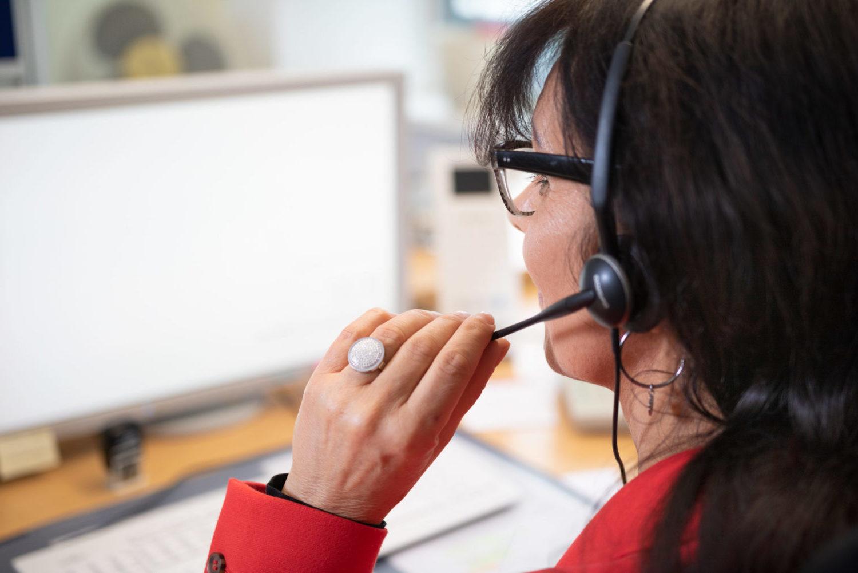 Schulterblick bei einer Telefonistin mit Kopfhörer samt Mikrophon