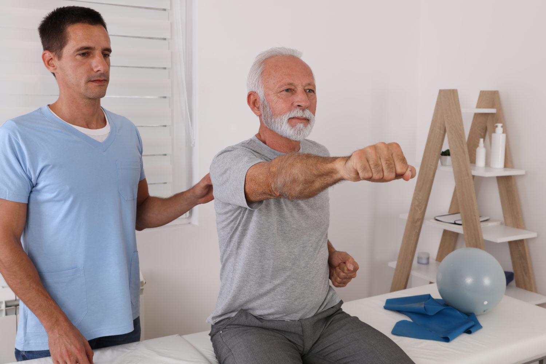 Grauhaariger Mann mit Bart bei der Physiotherapie mit seinem Therapeuten