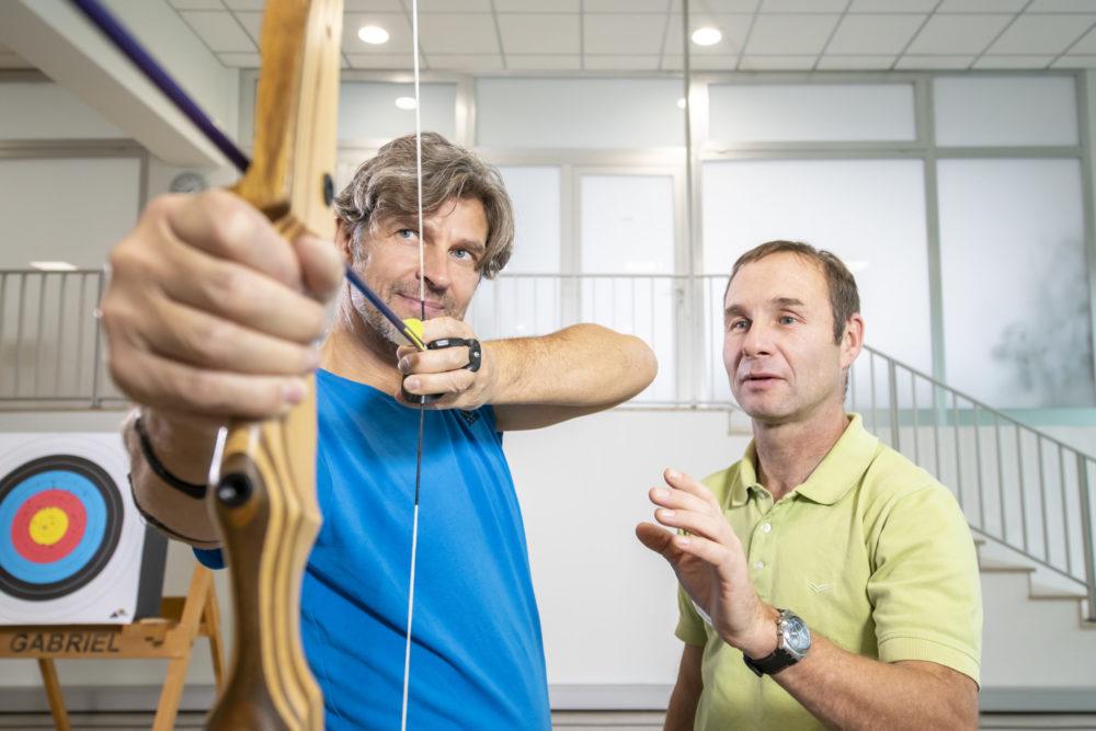 Mann mit Pfeil und Bogen und sein Trainer