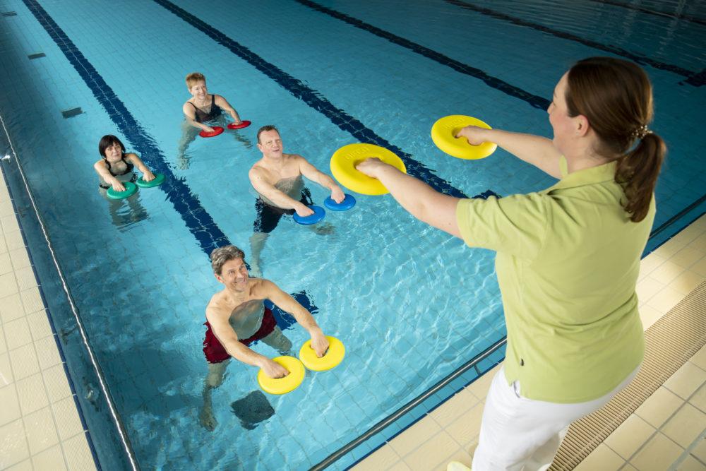 Zwei Männer und zwei Frauen bei der Wassergymnastik mit Trainerinungsbad