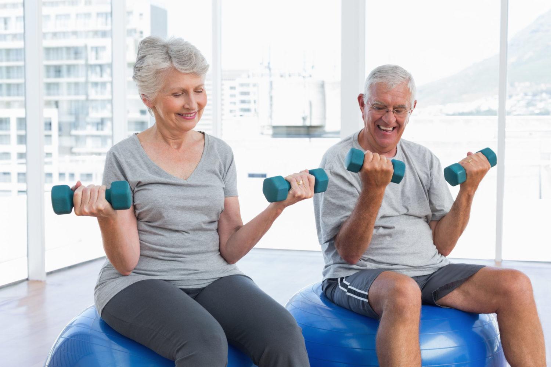 Grauhaariges Paar sitzt auf Gymnastikbällen und trainiert mit kleinen Hanteln