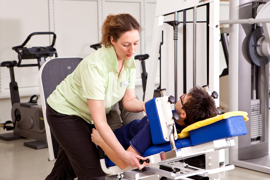 Trainerin und Frau beim Muskelaufbautraining auf einer Beinpresse