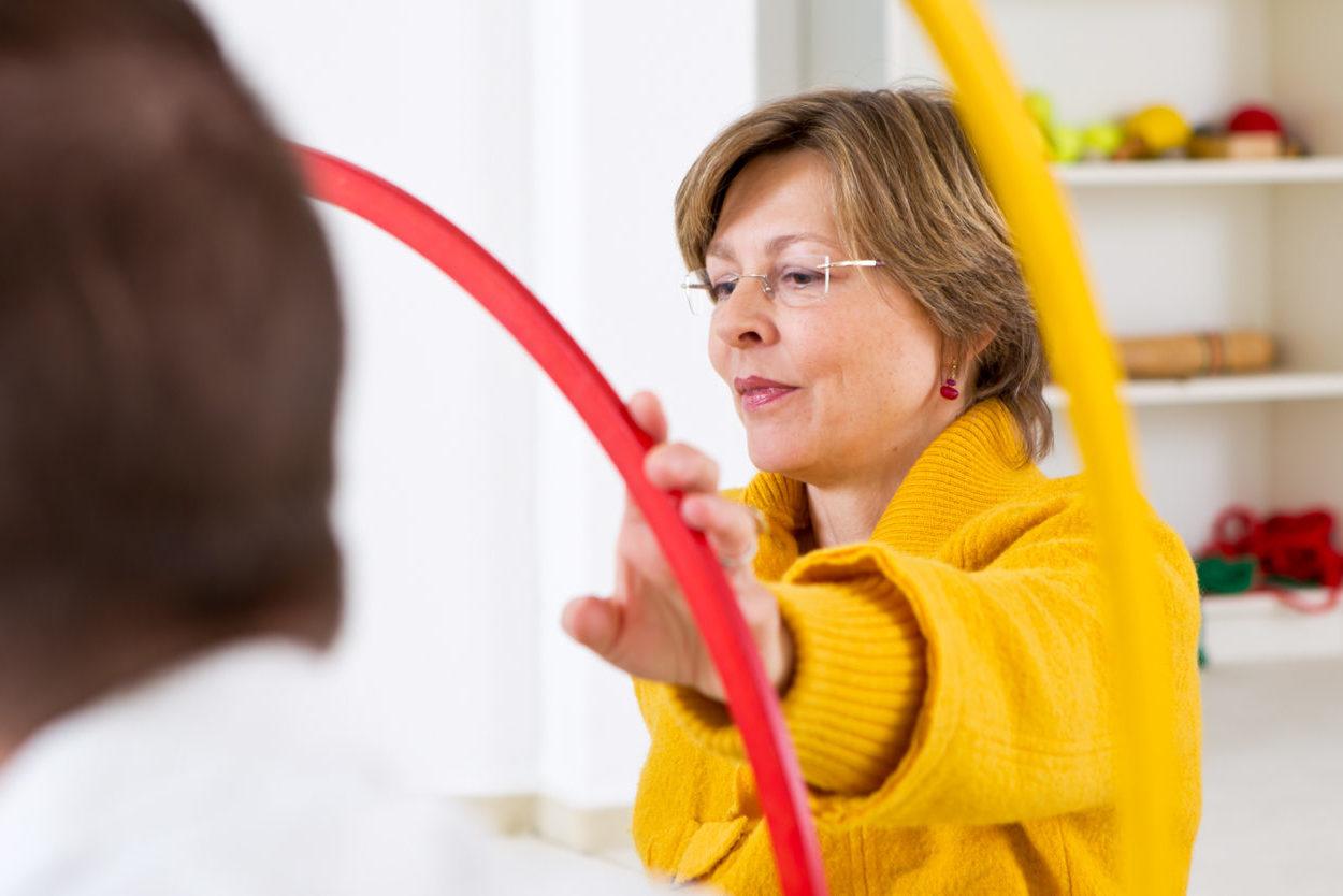 Frau im gelben Pullover greift nach einem roten Hula-Hoop-Reifen