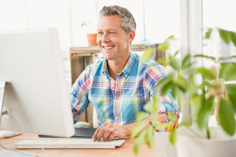 Mann mit graumelierten Haaren sitzt lächelnd am Bildschirmarbeitsplatz