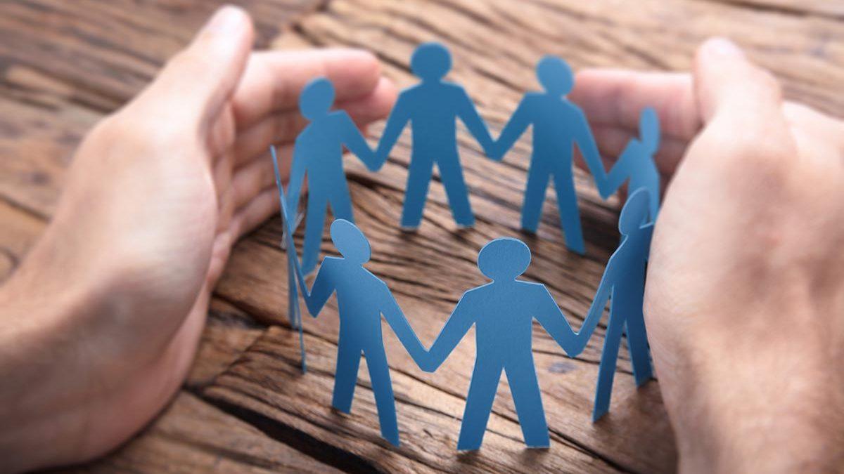 Männliche Hände legen sich schützend um einen Kreis aus acht Papiermännchen