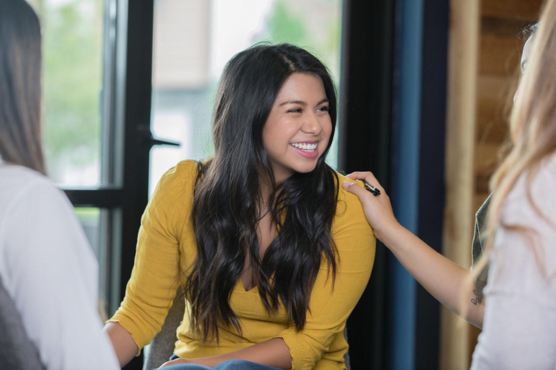 Junge dunkelhaarige Frau in gelber Bluse lächelnd während einer Gruppentherapie