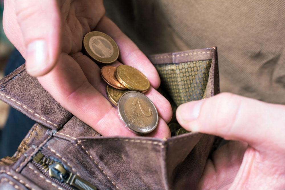 Männliche Hände werfen Euro-Münzen in ein braunes Portemonnaie